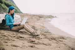 Freelancer girl working on laptop on beach Royalty Free Stock Image
