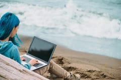 Freelancer girl working on laptop on coast Stock Images