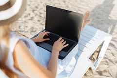 Freelancer girl working on vacation, in front of the beautiful sea, sitting with a laptop on the ocean stock images