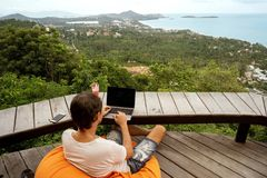 Freelancer guy sits working with a view of Samui island and the mountains royalty free stock image