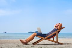 Freelancer, happy successful businessman on the beach. Freelancer, happy successful businessman with laptop on the beach, blue sky Royalty Free Stock Photo