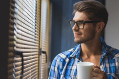 Freelancer holding cup of coffee and looking in the window Royalty Free Stock Photo