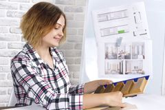 Freelancer interior designer working in design studio. Young freelancer interior designer working develop new appartment project in design studio. Women girl stock image