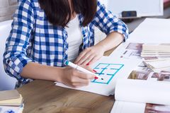 Freelancer interior designer working in design studio. Young freelancer interior designer working develop new appartment project in design studio. Women girl royalty free stock images