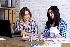 Freelancer interior designer working in design studio. Young freelancers interior designers working develop new appartment project in design studio. Two women stock photo