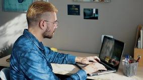 Freelancer joven hermoso con los vidrios y el pelo amarillo que trabajan en casa, usando un ordenador portátil Trabajo acertado e metrajes