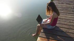 Freelancer kobieta robi jej akcydensowemu obsiadaniu na doku zbiory