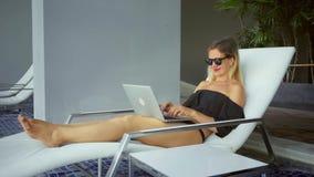 Freelancer kobiety obsiadanie na lounger blisko basenu działania na laptopie i, zwolnione tempo zdjęcie wideo