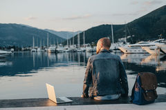 Freelancer with laptop resting time and enjoy sunset on the shor. E near the yacht boat at rest Stock Photo