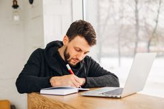 A freelancer with a laptop writes a note in a notebook. Young male businessman writing on a notepad in front of a laptop on wood desk in coffee cafe shop Stock Image