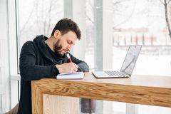 A freelancer with a laptop writes a note in a notebook. Young male businessman writing on a notepad in front of a laptop on wood desk in coffee cafe shop Stock Photo