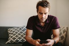 Freelancer looking at mobile phone sitting at home. Entrepreneur working on mobile phone sitting in the comfort of home. Man operating mobile phone while Royalty Free Stock Images