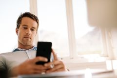 Freelancer looking at mobile phone sitting at home Stock Photography
