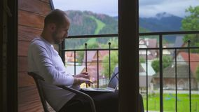 Freelancer man with a computer in a mountain village, against a background of a mountain landscape stock video