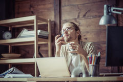Freelancer man at his working place thinking looking up. Royalty Free Stock Image