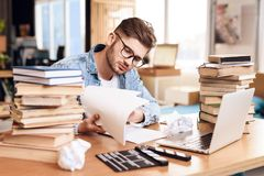 Freelancer man reviewing notes sitting at desk surrounded by books. Freelancer man in jeans shirt reviewing notes sitting at desk surrounded by books Royalty Free Stock Image