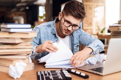Freelancer man reviewing notes sitting at desk surrounded by books. Freelancer man in jeans shirt reviewing notes sitting at desk surrounded by books Stock Image