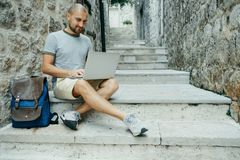 Freelancer man and a traveler working on a laptop in the street.  Stock Image