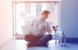 Freelancer man using laptop computer and cup of coffee. Handsome young freelancer man using laptop computer and cup of coffee sitting at floor near a dog inside stock photo