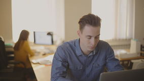 Freelancer Man Working at Studio loft. In the picture are a man who works with a laptop. Outside the focus is a modern office with a young woman. The camera is stock video footage