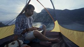 Freelancer Man Working Using Laptop Sitting In A Camping Tent On The Beach. Freelancer working on new startup project