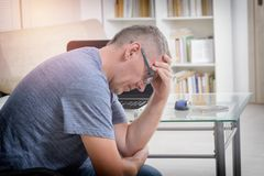 Freelancer man at workplace in office holding his head on hands Stock Images