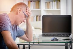 Freelancer man at workplace in office holding his head on hands Stock Image