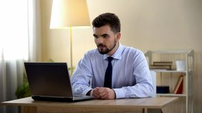 Freelancer masculino novo que tem a entrevista de trabalho no portátil em casa, desemprego fotografia de stock royalty free