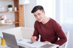 Freelancer masculino positivo que destaca palavras no jornal imagens de stock royalty free