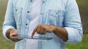 Freelancer masculino que trabalha na tabuleta fora, arquivos zumbindo das mãos no écran sensível filme