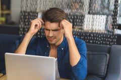Freelancer novo na frente de um portátil que tenta pensar Fotografia de Stock Royalty Free