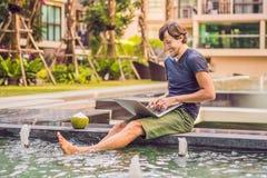 Freelancer novo que trabalha em férias ao lado da piscina fotografia de stock