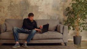 Freelancer ocupado con el funcionamiento del ordenador portátil en inicio almacen de metraje de vídeo
