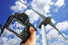 Freelancer photographer with DSLR camera taking picture of wind turbine in a sunny day royalty free stock images