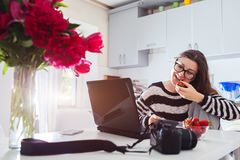 Freelancer photographer working at home. Woman works on laptop using camera and pen tablet. Start up. Freelancer photographer working in kitchen having a snack Royalty Free Stock Photography