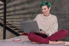 Freelancer pisarski ono uśmiecha się podczas gdy czytający przegląd jej opowieść obrazy royalty free