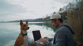 Freelancer pracuje na jego laptopie plenerowym obok jeziora, siedzi na stawie zbiory