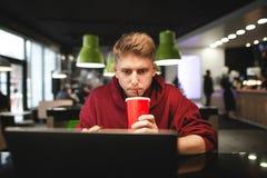 Freelancer pracuje na laptopie w kawiarni na ekranie patrzeje skupiającym się i pije koli Praca w kawiarni fotografia stock