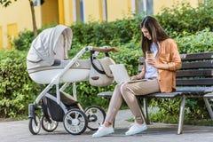 freelancer pracuje z laptopem na ławce blisko wózka spacerowego w parku i trzyma kawę obraz royalty free