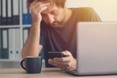 Freelancer preocupante que lee el mensaje del SMS de las malas noticias imagen de archivo