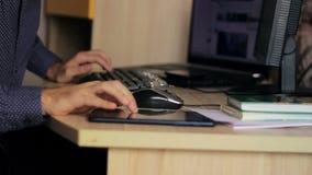 Freelancer que trabaja con un ordenador portátil y una tableta en almacen de metraje de vídeo