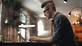 Freelancer que trabaja difícilmente en el café almacen de video