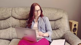 Freelancer red haired female sitting oh sofa, working and answering phone. Young woman in glasses reading, working with laptop, and having phone conversation stock video