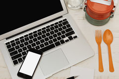 Freelancer`s lunch break. Lunch on the job - laptop and cell phone and food containers, glass of water cutlery on the one table royalty free stock photo