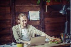 Freelancer som arbetar på träskrivbordet som drar handen för smörgås Royaltyfri Fotografi