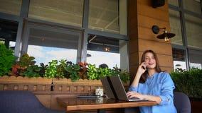 Freelancer som talar vid smartphonen och arbete med bärbara datorn på kafét stock video