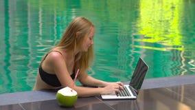 Freelancer sonriente feliz de la mujer que trabaja en un ordenador portátil que se sienta en una piscina en las zonas tropicales almacen de video