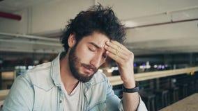 Freelancer subrayado con el dolor de cabeza que se sienta en café metrajes