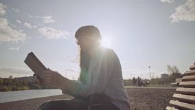 Freelancer with tablet sits on wooden deck chair on pebble beach in cool day. Young woman in glasses uses tablet while sitting on wooden deck chair on pebble stock video