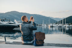 Freelancer taking photo and working on laptop on the shore near. The yacht boat at rest Stock Image
